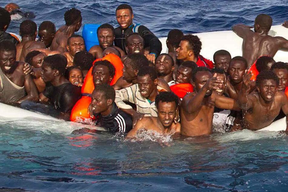 Flüchtlinge auf dem Mittelmeer in einem sinkenden Schlauchboot.