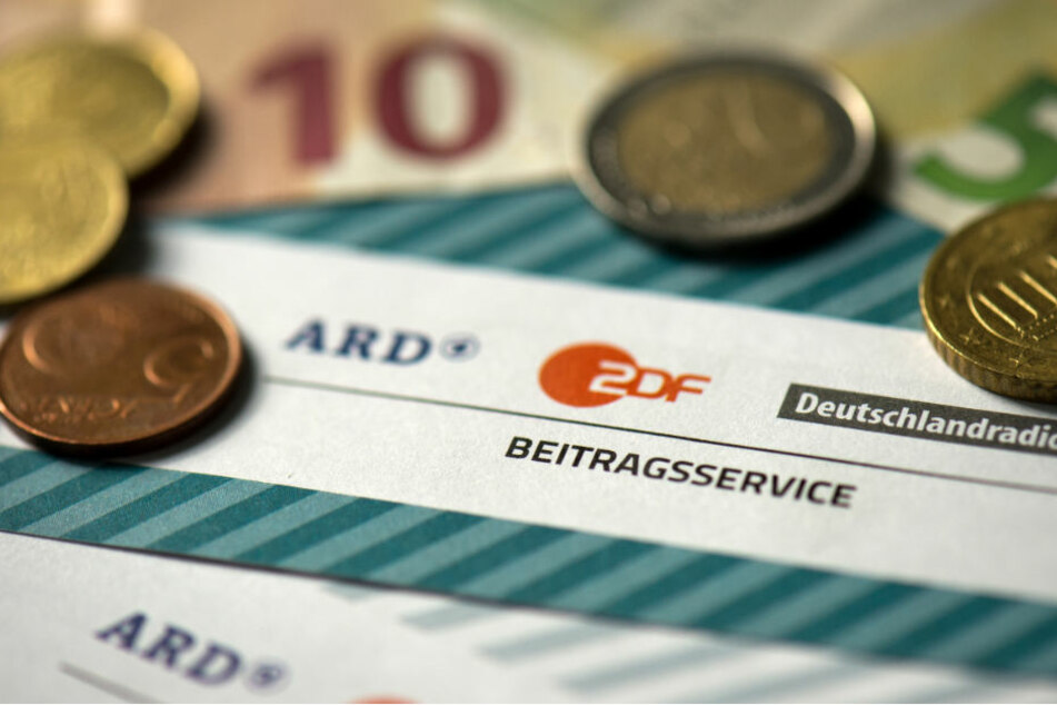 Münzgeld liegt auf Formularen für den Rundfunkbeitragvon ARD, ZDF und Deutschlandradio.