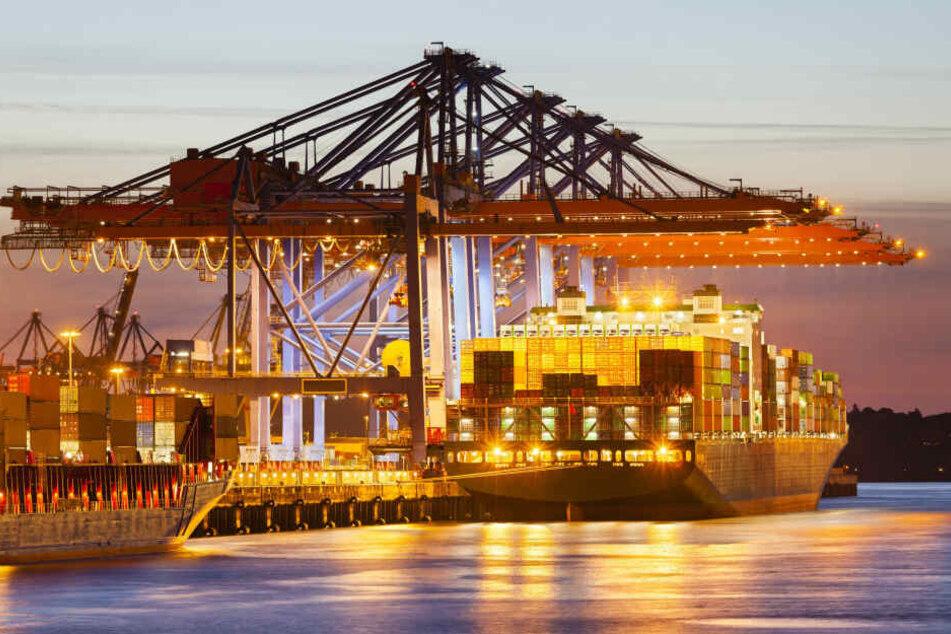 Ein Containerschiff liegt in der Abenddämmerung an einem Hamburger Terminal.