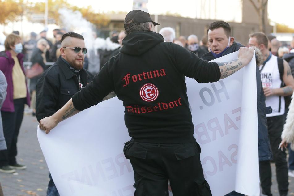 Demonstranten stehen auf dem Johannes Rau Platz neben Organisator Dominik Roeseler (r) bei einem Protest gegen die Corona-Maßnahmen.