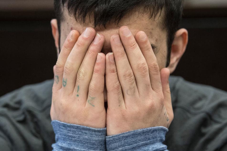 Der Angeklagte Ali B. hält sich während des Prozesses die Hände vor das Gesicht.