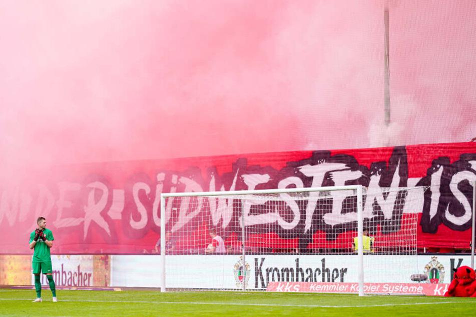 Kaiserslauterns Torwart Lennart Grill betrachtet den dichten weiß-roten Rauch auf Kaiserslauterns Fantribüne.