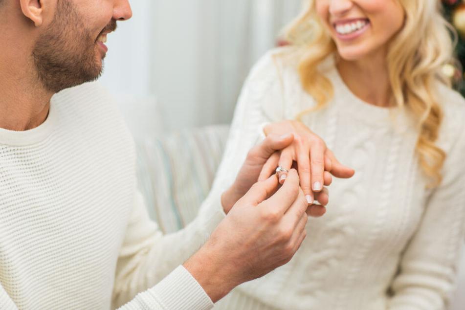 Ein Mann legt seiner Freundin einen Verlobungsring an.