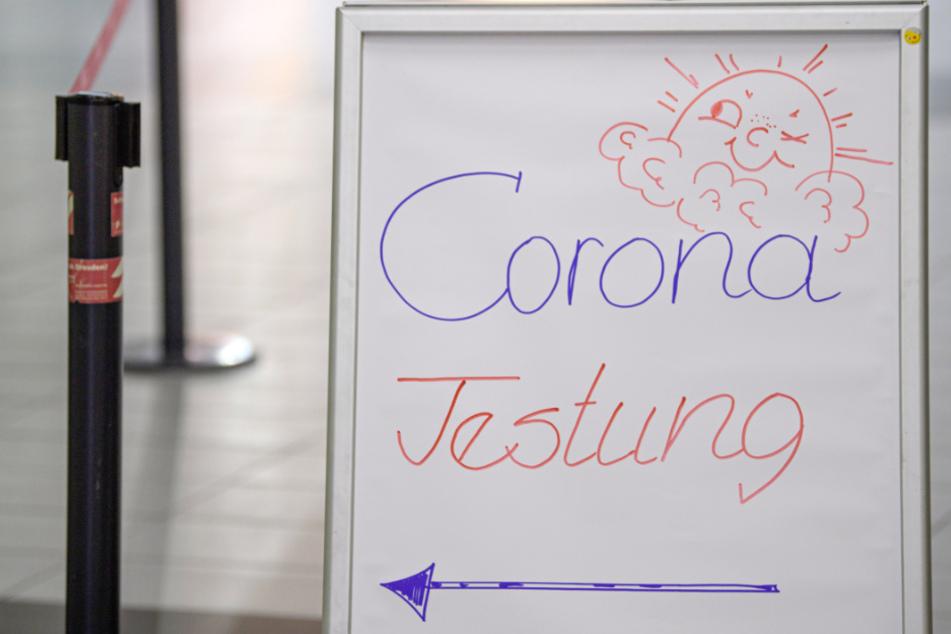 Ein Aufsteller verweist auf die Corona-Teststation am Dresdner Flughafen.