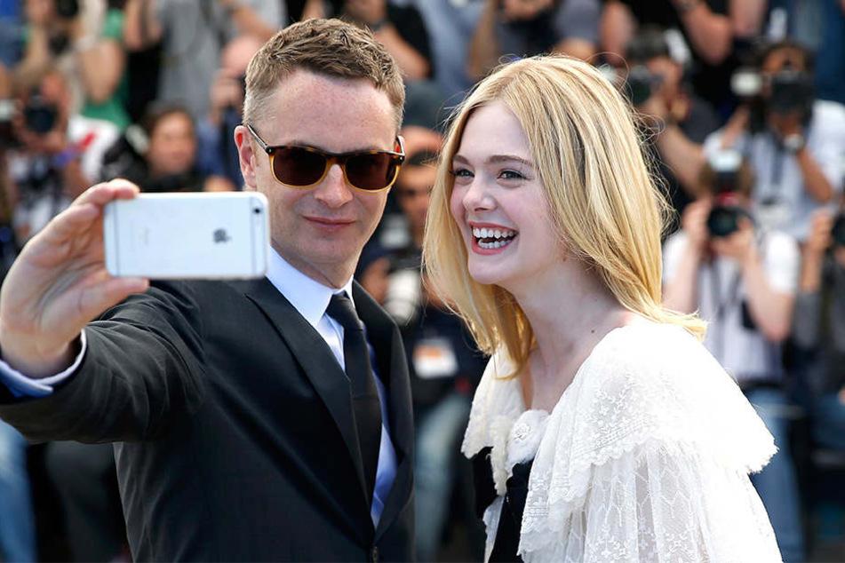 Die amerikanische Schauspielerin Elle Fanning und der dänische Regisseur Nicolas Winding Refn machen trotzdem ein Selfie von sich.