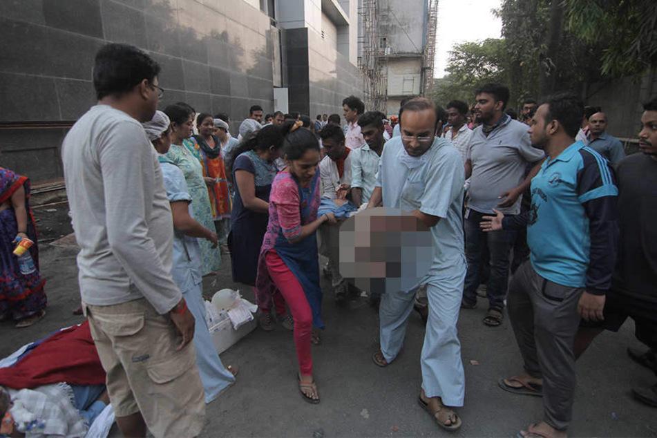 Eine verletzte Person wird aus dem brennenden ESIC Kamgar Krankenhaus geborgen.