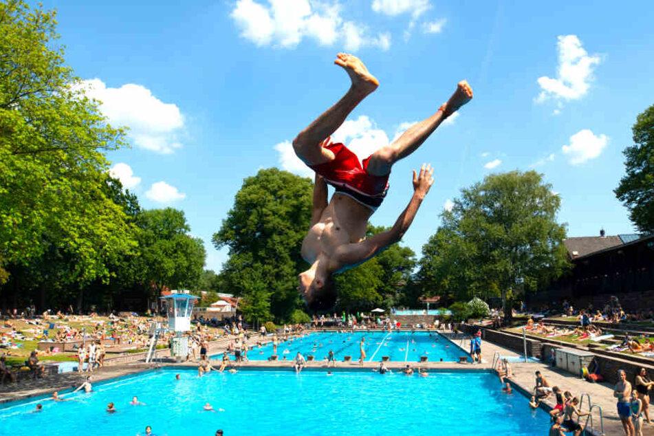 """Ein junger Mann springt im """"Kaifu-Bad"""" im Stadtteil Eimsbüttel vom Drei-Meter-Brett, während sich hinter ihm viele Besucher tummeln."""