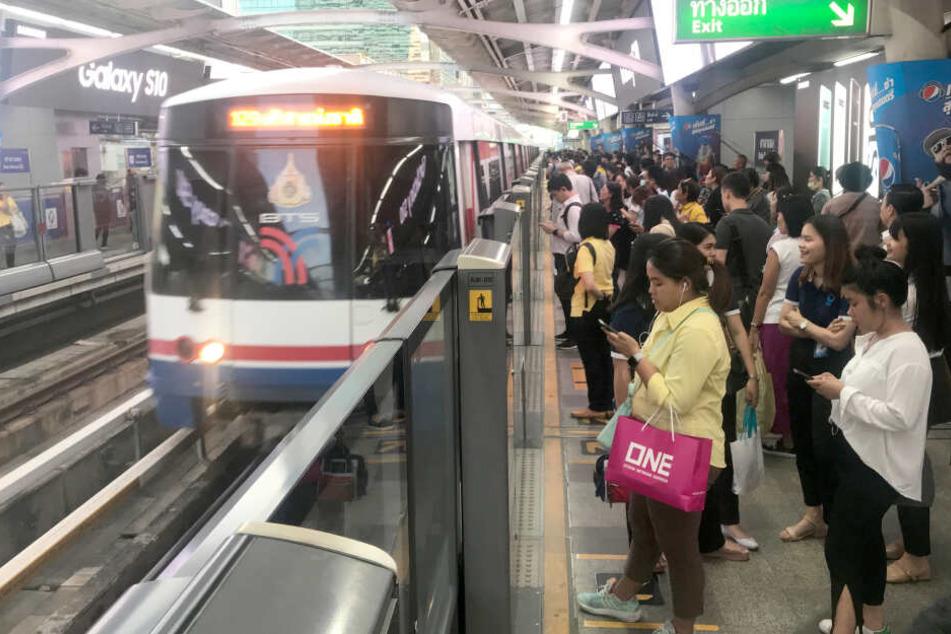 Hohe Glasscheiben an einem Bahnsteig in Bangkok (Thailand) des Bahnhofs Salah Daeng sorgen dafür, dass Passagiere bei der Einfahrt eines Nahverkehrszuges nicht auf die Gleise fallen oder gestoßen werden können.