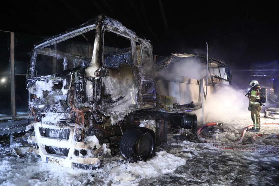 Feuerwehrleute löschen den völlig zerstörten Laster.