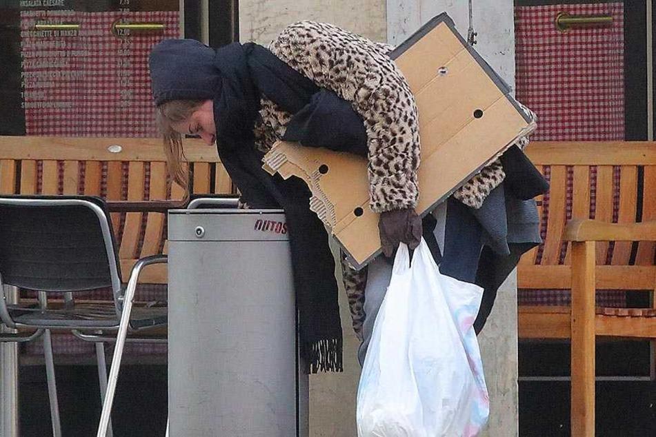 Mit Schal, Pappe und Schlafsack unterwegs: Mülleimer nach Brauchbarem zu durchwühlen ist sogar noch ekliger, als man es sich vorstellt.