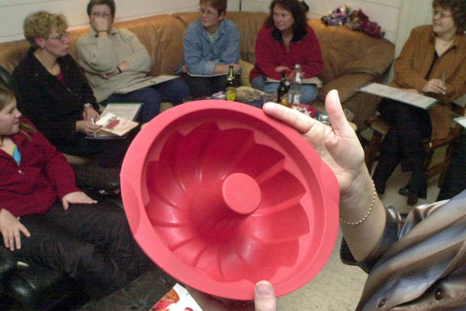"""Eine rote Kuchenbackform wird von einer Verkäuferin bei einer """"Party"""" im Wohnzimmer angepriesen. (Archivfoto)"""