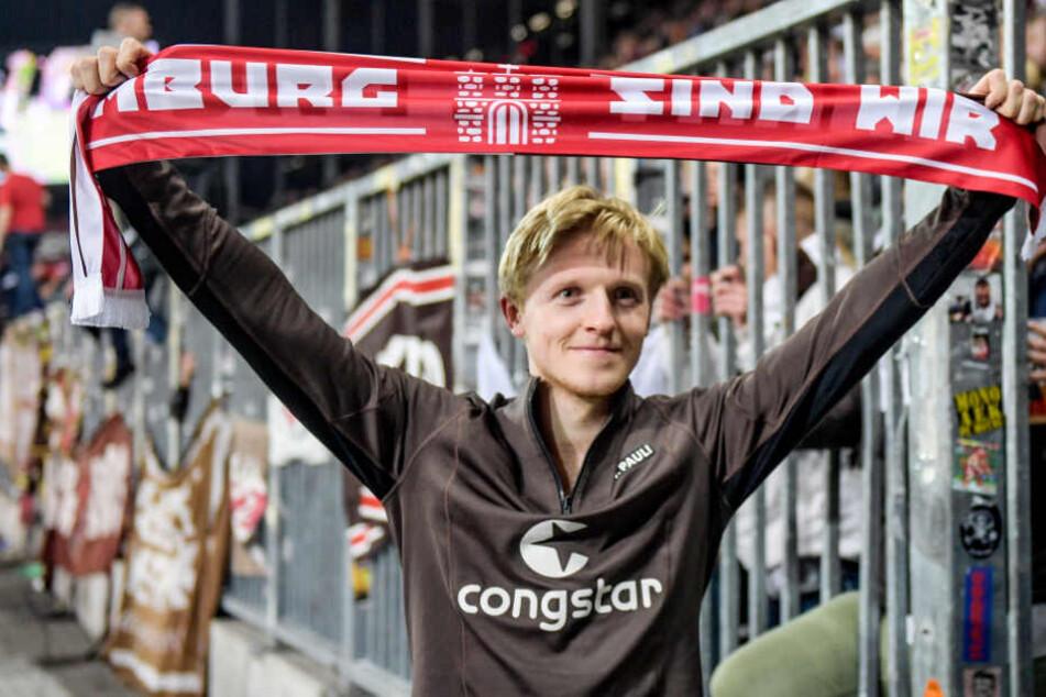 """St. Paulis Mats Möller Daehli hält vor der Fankurve einen Schal mit der Aufschrift """"Hamburg sind wir"""" in die Höhe. (Archivbild)"""