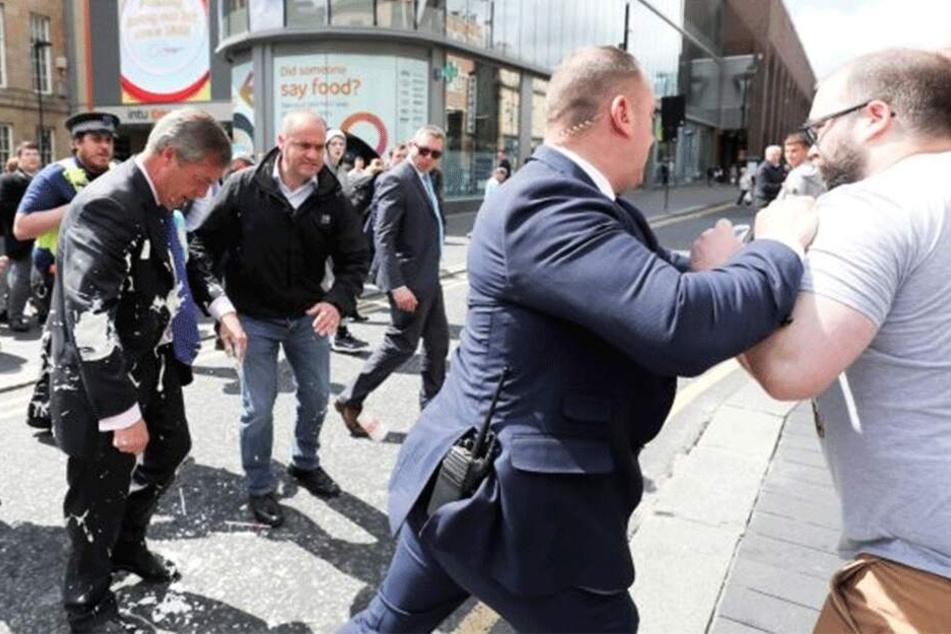 Kurz nach der Attacke blickt Farage betreten zu Boden, während Bodyguards den Angreifer festsetzen.