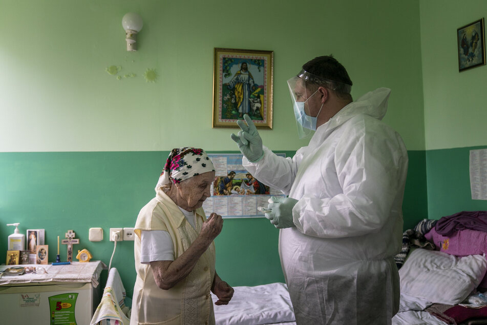 Pater Jaroslaw Rokhman, Priester der griechisch-katholischen Kirche in Ungarn, segnet in Schutzkleidung und Gesichtsvisier zum Schutz vor einer Ansteckung mit dem Coronavirus eine Patientin eines Hospizes.