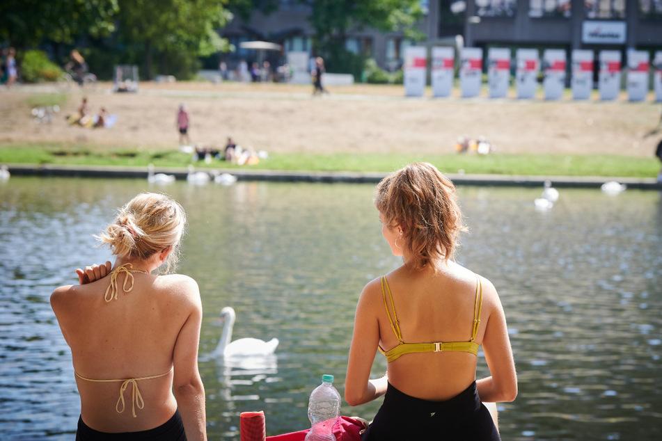 Zwei junge Frauen sitzen auf der Wiese am Landwehrkanal in der Sonne. Bereits das vergangene Wochenende brachte Temperaturen bis über 30 Grad.