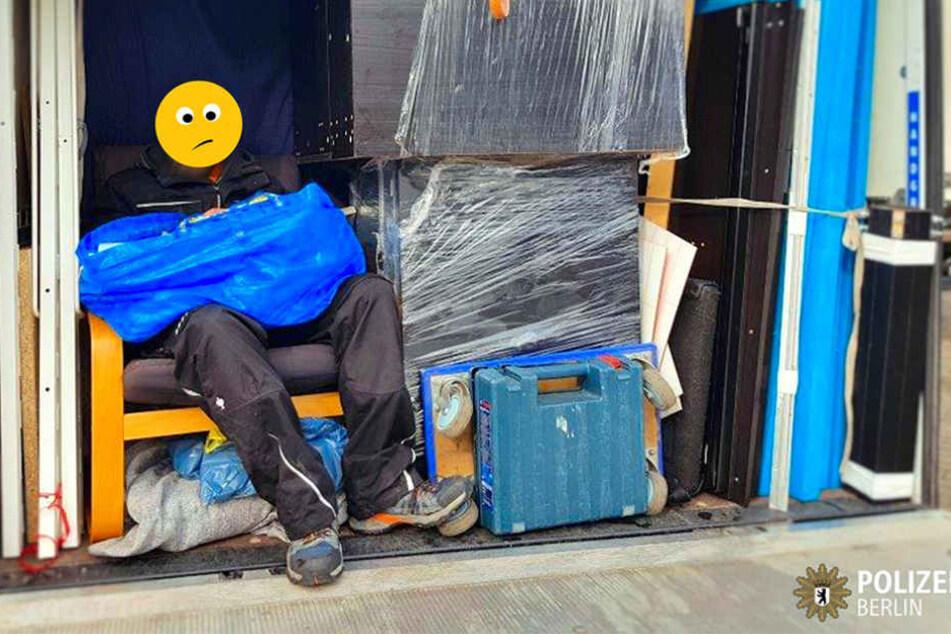 Auf der Ladefläche eingepfercht, sitzt der Mann auf einem Polstersessel.