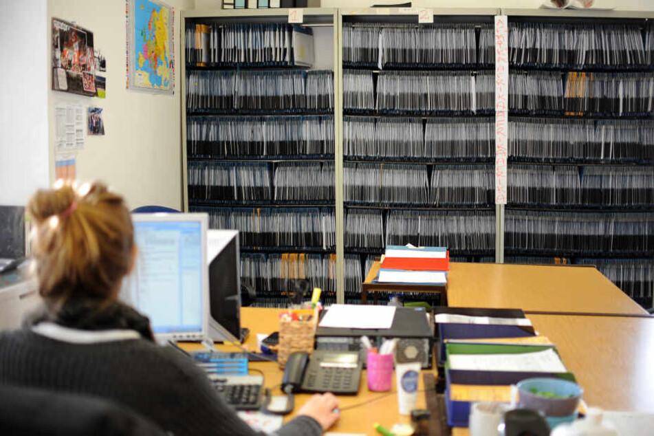 Eine Mitarbeiterin arbeitet vor Regalen voller Akten von Antragstellern in einem Amt. (Archivbild)