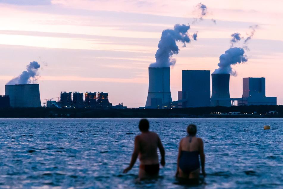Neue und alte Lausitz-Welt: Ein Paar badet im Bärwalder See vor der Kulisse des Boxberger Kraftwerks. Seenflutung, Naherholung und Tourismus werden eine tragende Säule des Nach-Kohle-Zeitalters sein.