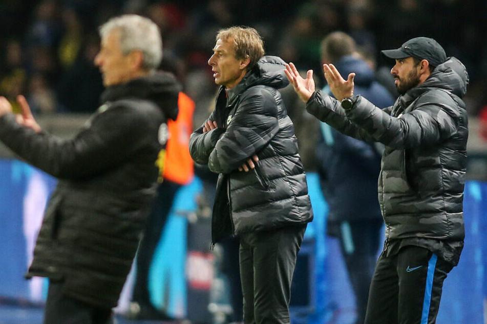 Berlins Cheftrainer Jürgen Klinsmann (m) und Co-Trainer Alexander Nouri (r) stehen gestikulierend am Spielfeldrand.