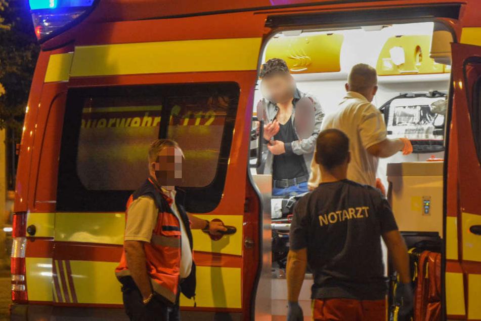 Blutverschmiert steht ein Mann im Rettungswagen auf dem Hasselbachplatz. Ein 44-jähriger Türke wurde bei der Auseinandersetzung schwer verletzt.