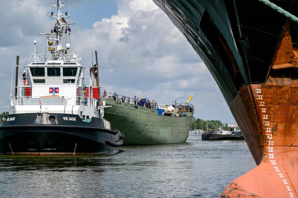 Ein Schlepper zieht den Rumpf der Gorch Fock über die Weser.