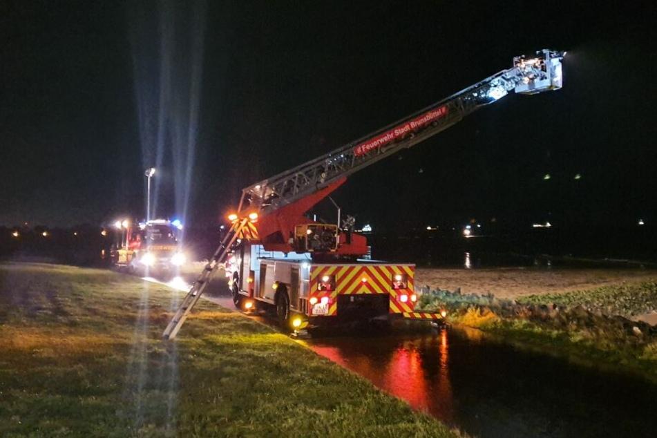 Feuerwehrfahrzeuge stehen an einem Deich bei Brunsbüttel und suchen nach der Mutter und ihrem Sohn.