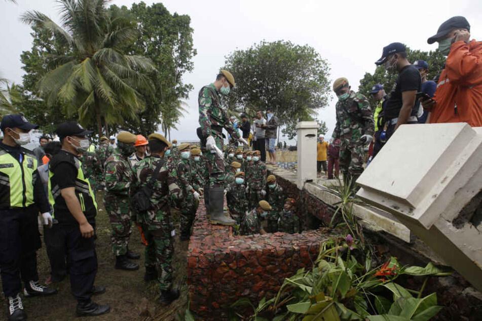 Indonesische Soldaten ud Rettungskräfte suchen in einem Strandressort nach Opfern der Tsunami-Katastrophe.