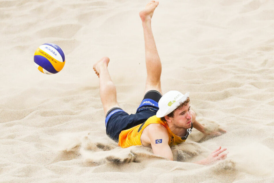 Lars Flüggen landet bei einer Aktion im Sand.
