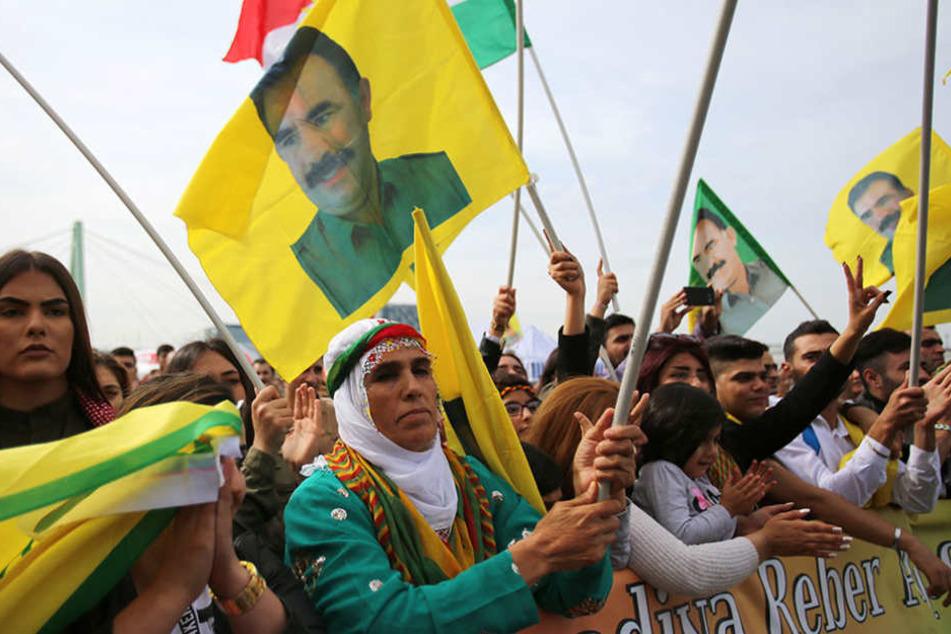 Teilnehmer der Kundgebung schwenken Fahnen mit dem Bild des PKK-Gründers Öcalan.