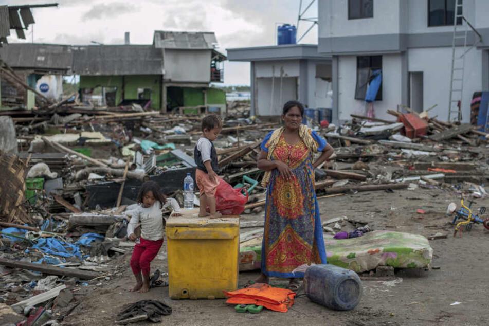 Eine Frau und ihre Kinder stehen zwischen den Trümmern in einem vom Tsunami verwüsteten Dorf.