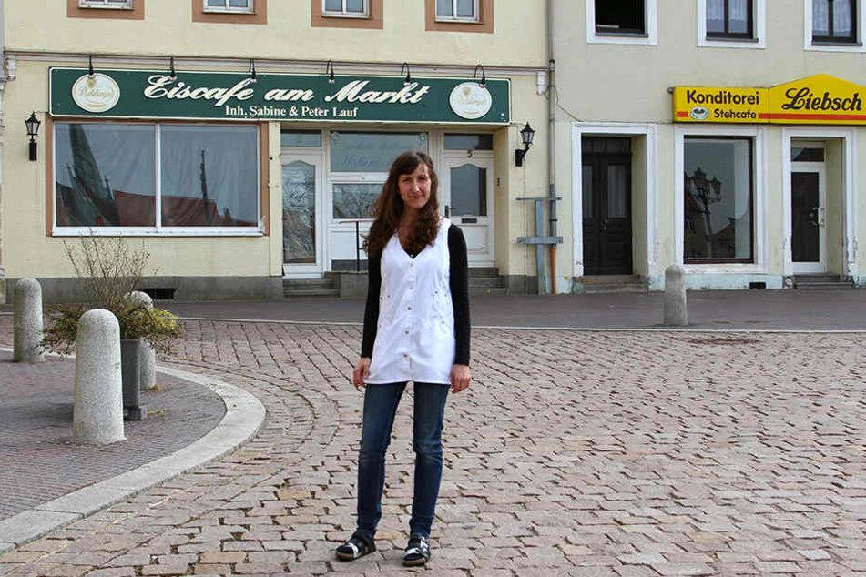 Apotheken-Angestellte Annika Ray bedauert, dass mit der Schließung des Stadtcafés jetzt auch der Freisitz vom Markt verschwand. Das Eiscafé im Hintergrund ist schon lange dicht, ebenso der Bäckerladen daneben.