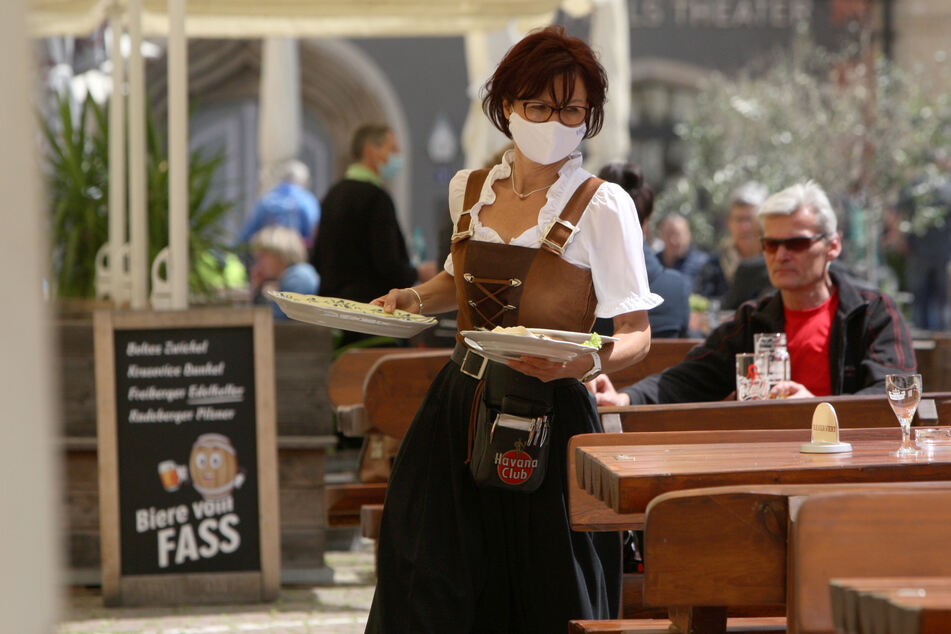 Eine Kellnerin mit Mundschutz bewirtet die Gäste vor der Gaststätte Ratsherrenstuben in Pirna.