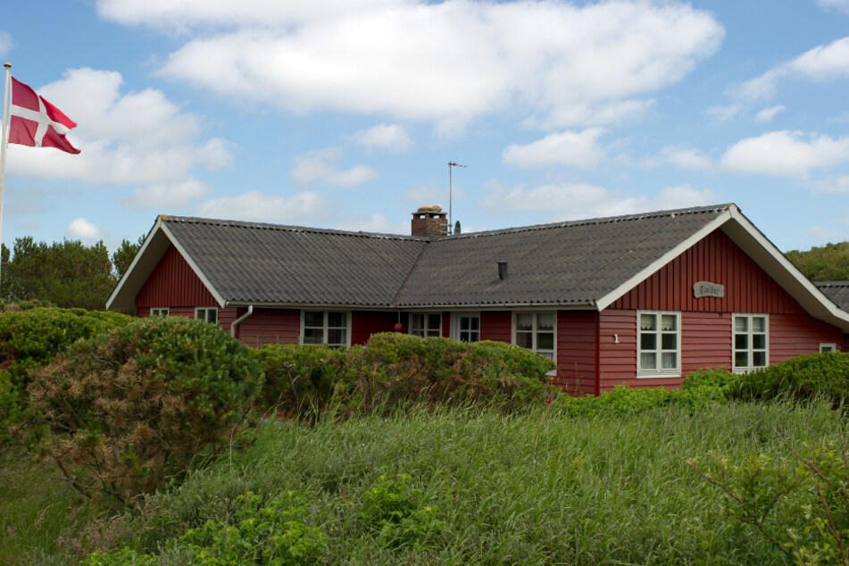 Dänemark, Henne Strand: Ein dänische Fahne weht an einem Ferienhaus in Henne Strand, einem Ferienort an der dänischen Westküste, nördlich von Esbjerg.