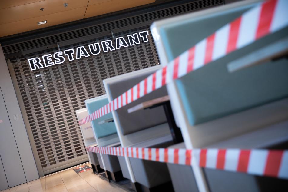 Ein Restaurant ist in einer Passage mit Flatterband abgesperrt.