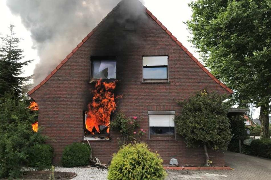 Flammen schlagen aus dem Zweifamilienhaus.