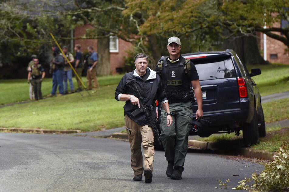 Polizeibeamte durchsuchen das Foxhall-Viertel hinter der Mount Tabor High School. Vermutlich handelt es sich bei dem Täter um einen anderen Schüler.