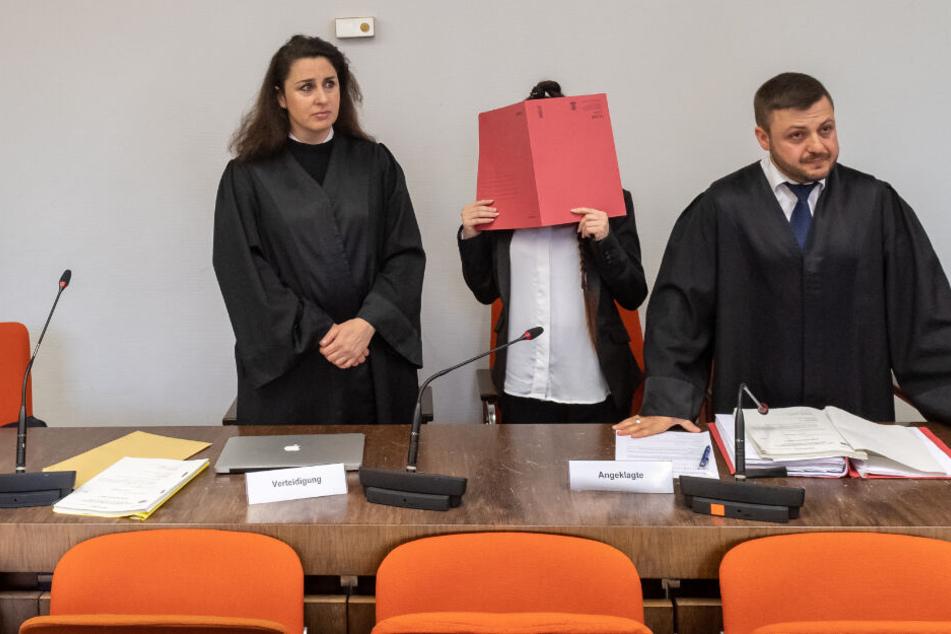 Archiv: Die Angeklagte (2.v.r) steht mit einem roten Aktendeckel vor ihrem Gesicht zu Prozessbeginn zwischen den Anwälten Sera Basay-Yildiz (l) und Ali Aydin (r) im Gerichtssaal.