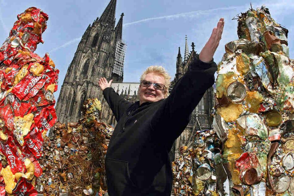HA Schult posiert im April 2014 mit einigen seiner Müllmenschen vor dem Kölner Dom.