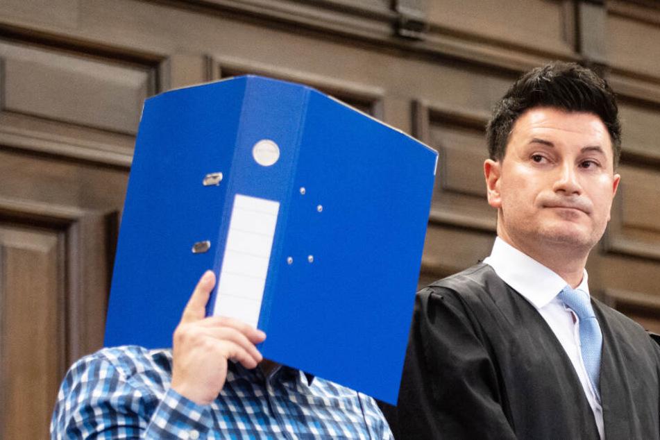 Der Angeklagte verbirgt sein Gesicht zu Prozessbeginn hinter einem Aktenordner. Daneben steht sein Verteidiger Haydar Güler.