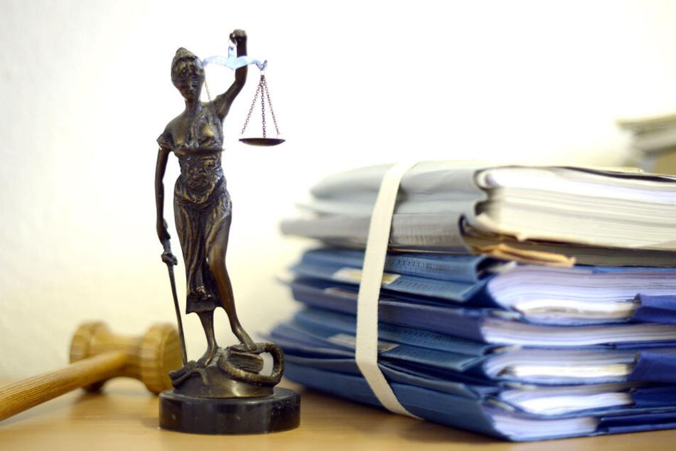Ein Modell der Justitia steht in einem Raum eines Richters neben einem Holzhammer und einem Aktenstapel (Symbolbild).