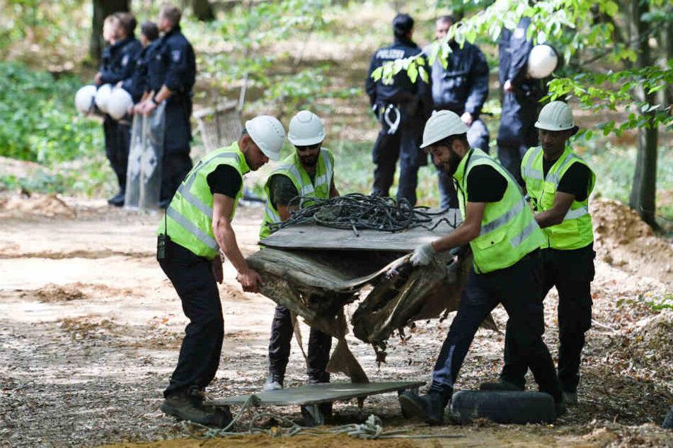 RWE-Mitarbeiter und die Polizei bei der Bergung des Autos im Hambacher Forst.