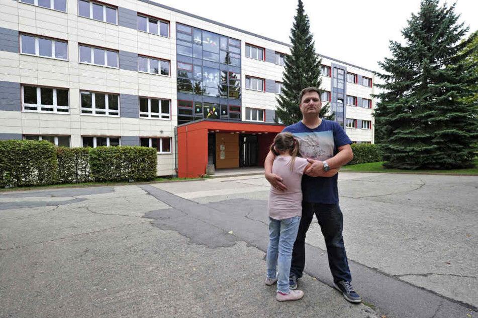 Andreas Lindner (41) und seine Tochter vor der Charles-Darwin-Grundschule. Hier soll es auf dem Weg zum Hort zu der Bedrohung gekommen sein.