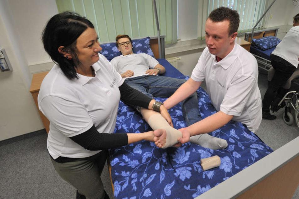 Ausbilderin Steffi Hilpert zeigt Marc Plihal in der WBS-Pflegeschule das Anlegen eines Verbands.