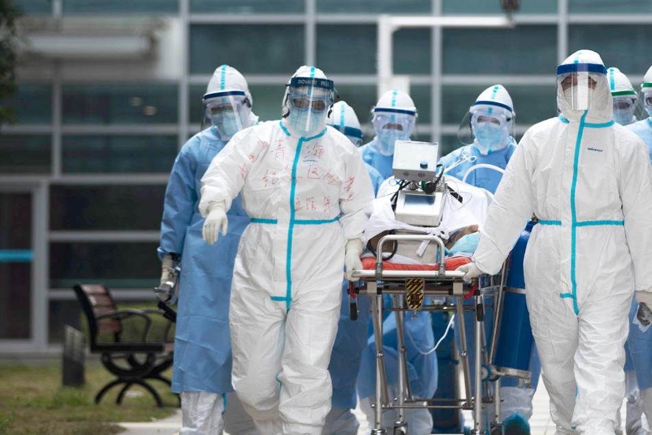 Medizinisches Personal in Schutzkleidung transportiert einen COVID-19-Patienten. © Fei Maohua/XinHua/dpa