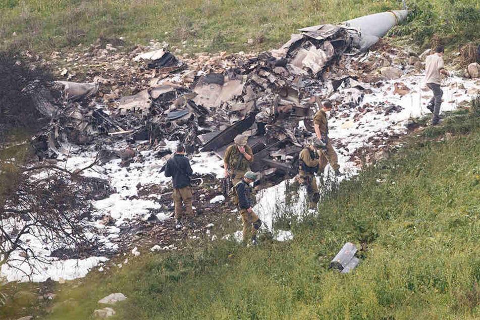 Israelische Sicherheitskräfte stehen am 10.02.2018 neben den Überresten eines israelischen F-16 Kampfflugzeugs an der Absturzstelle bei Harduf.