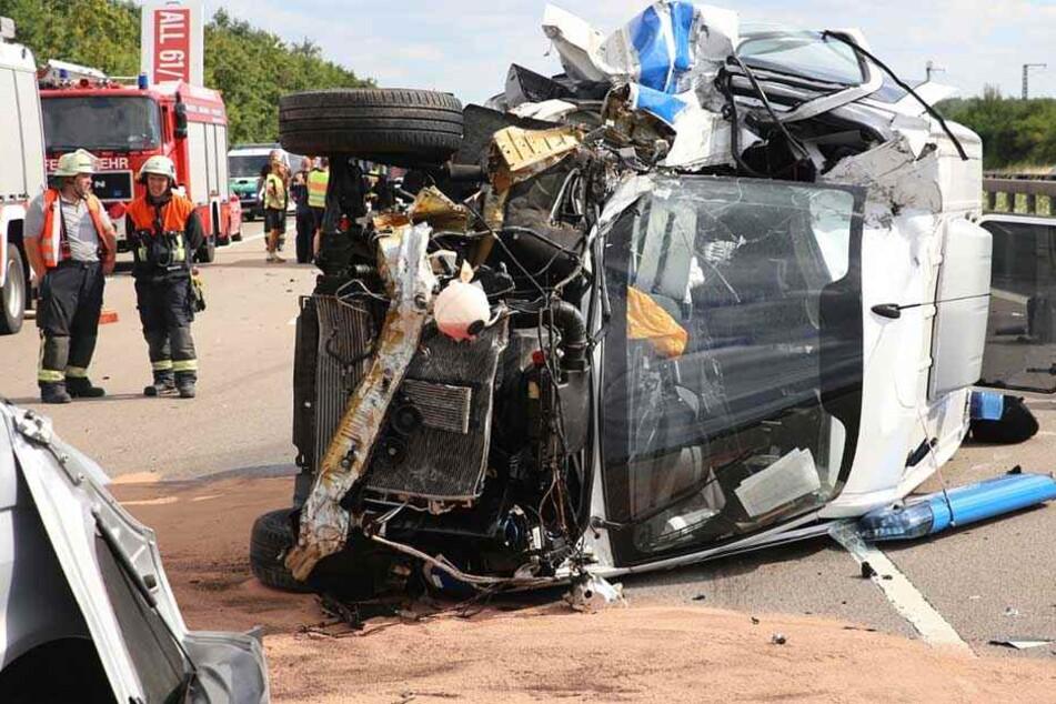 Der Mannschaftswagen der Bereitschaftspolizei liegt zerstört auf der Seite.