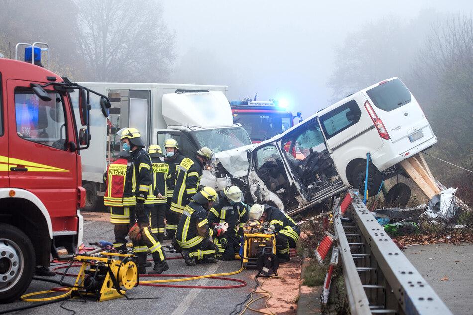 Einsatzkräfte der Feuerwehr arbeiten auf der Bundesstraße 404 zwischen den Orten Grande und Trittau an der Unfallstelle.