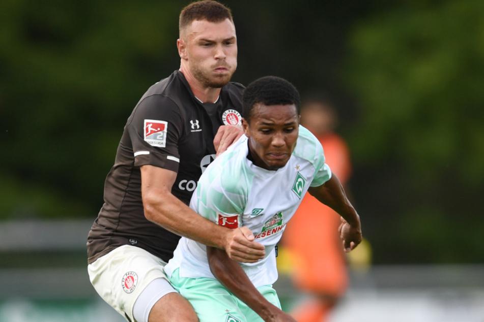 Werders Felix Agu (r) und St. Paulis Maximilian Dittgen in Aktion. Weil er weiter positiv auf das Coronavirus getestet wurde, wird Felix Agu dem Fußball-Bundesligisten Werder Bremen noch länger fehlen.
