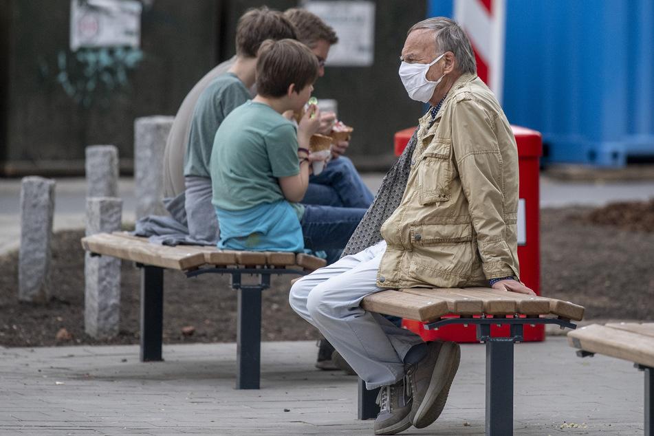 Ein Mann trägt eine Nase-Mund-Schutzmaske, während er neben Jugendlichen auf einer Bank sitzt.