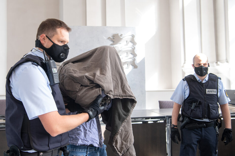 Der Angeklagte versteckte sich am Eröffnungstag unter einer Jacke.